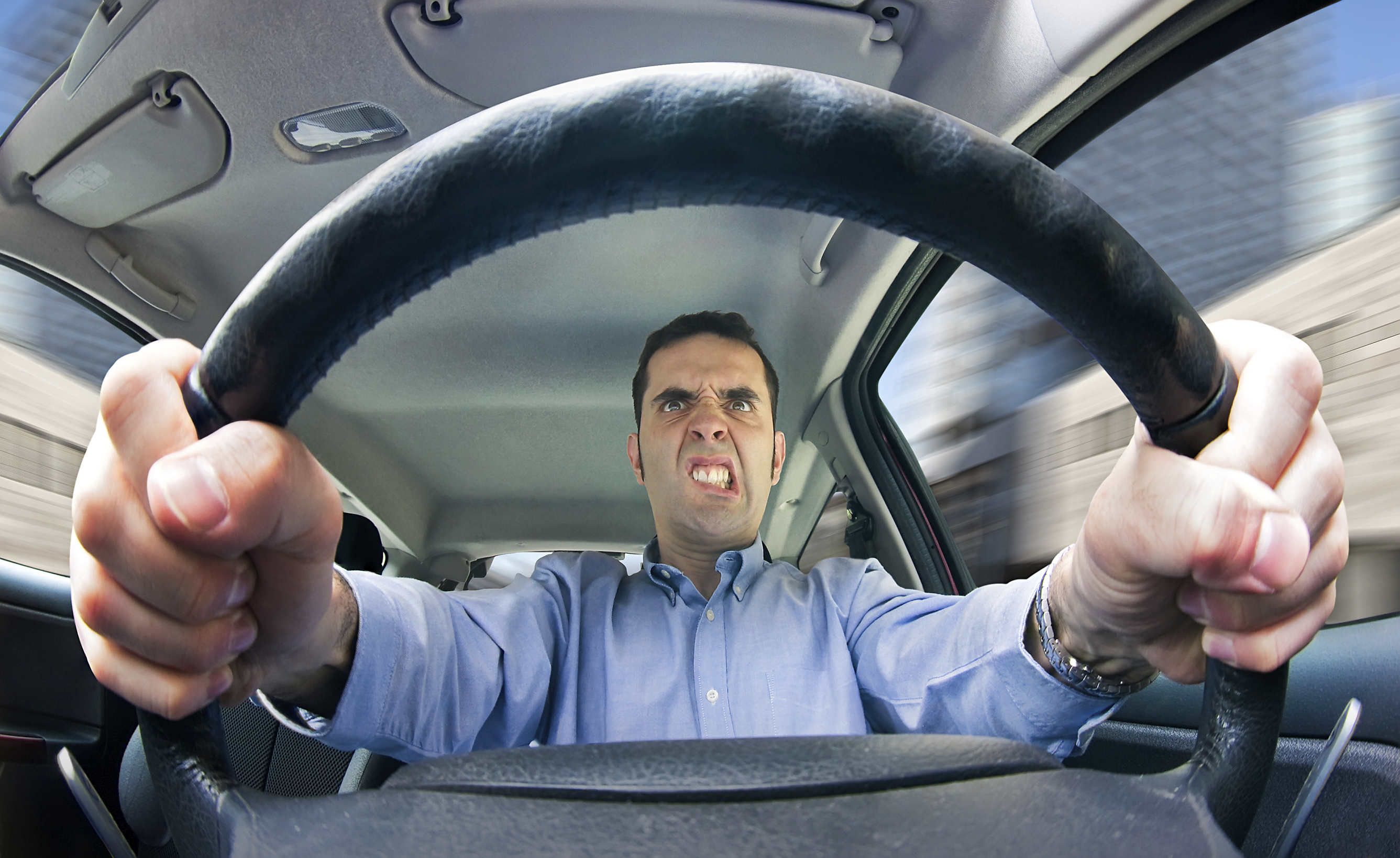 road rage no harm spilt a furious man driving as seen from behind the wheel shot using a very