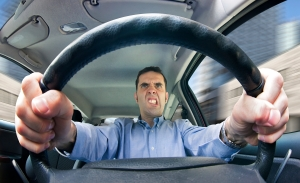 A furious man driving, as seen from behind the wheel. Shot using a very wide fisheye lens.